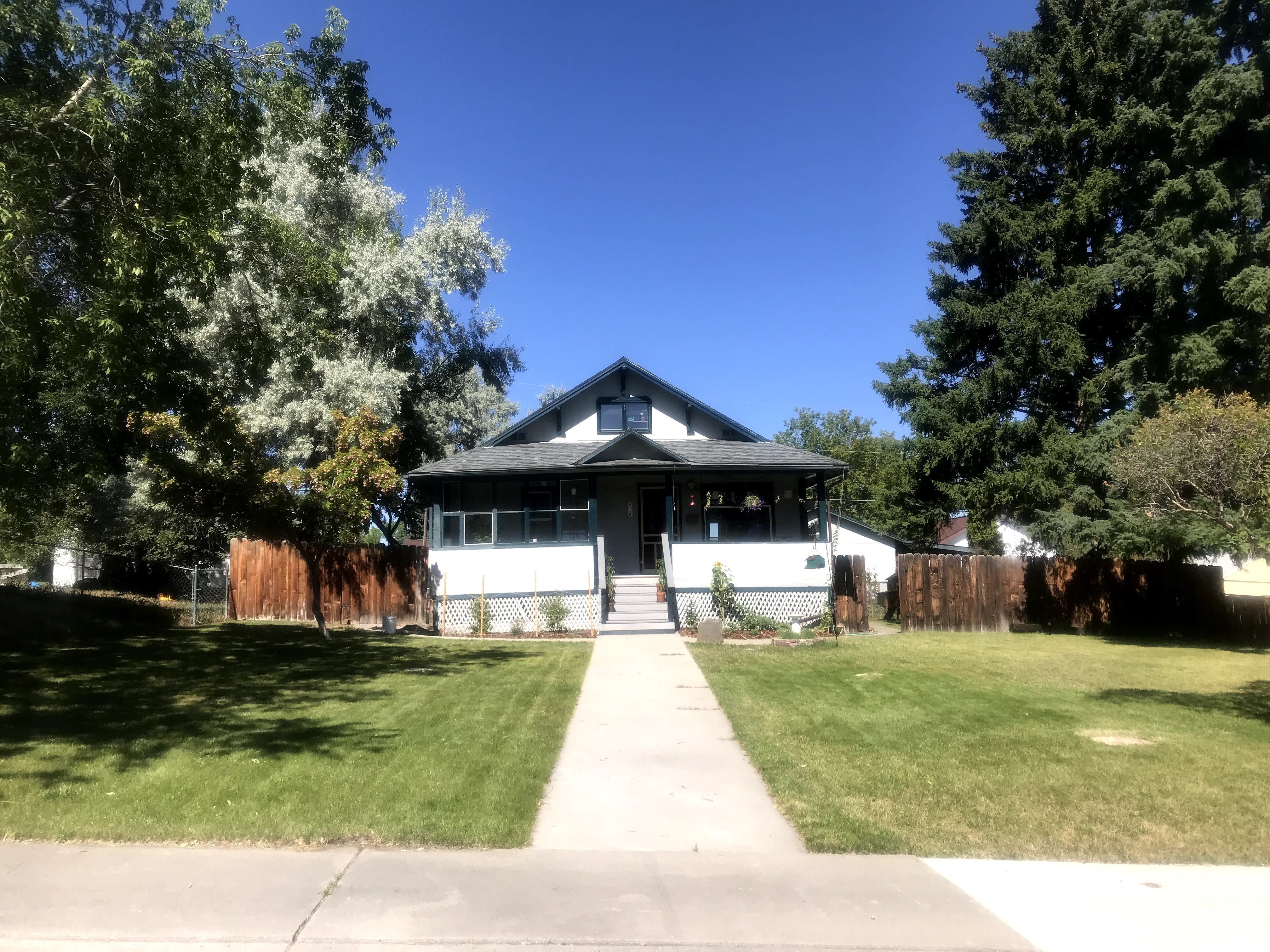 Stucco bungalow with large, empty front lawn and some small plantings.
