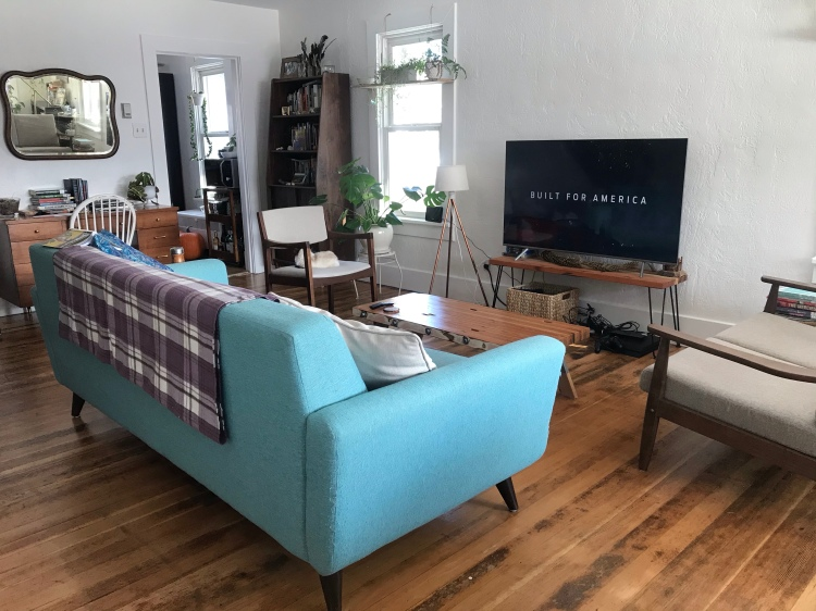 """Living room with teal couch and large flat screen that says """"built for America."""""""