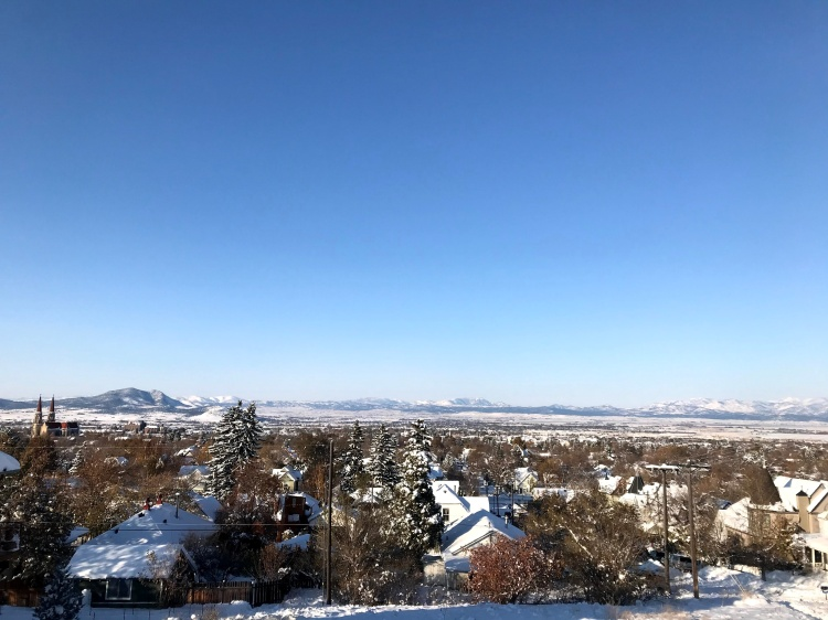 Snow covered town as viewed from a tall hill overlooking a wide valley with other mountains in the distance.