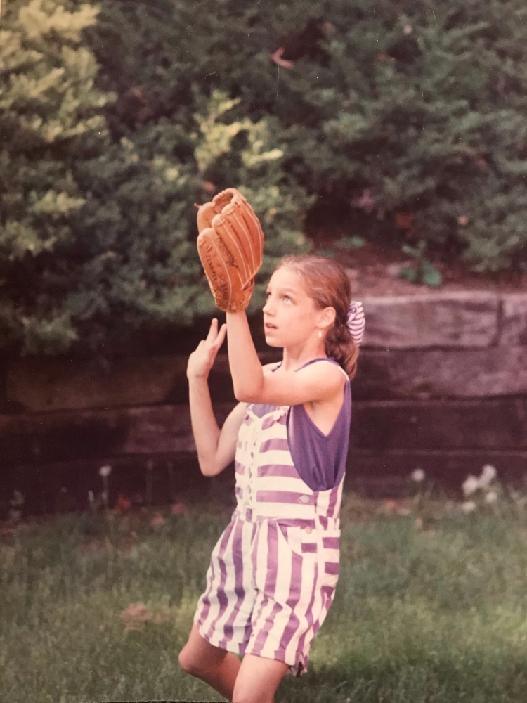 Young girl in purple and white striped overalls with a baseball glove preparing to catch a ball.