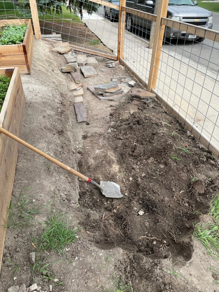 Large dugout area with some stones stacked between a fence and some garden beds