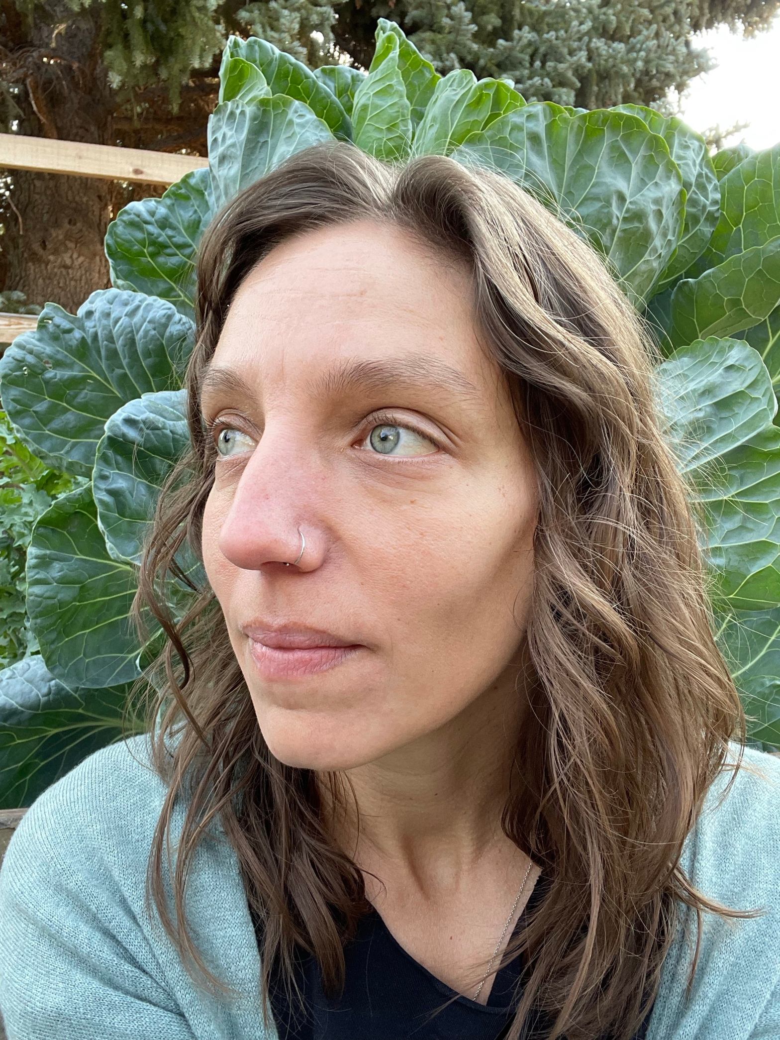 selfie style image of a white woman with brown hair and green eyes who has given up on plucking her eyebrows, looking to the side, with large Brussel sprout growing in the background