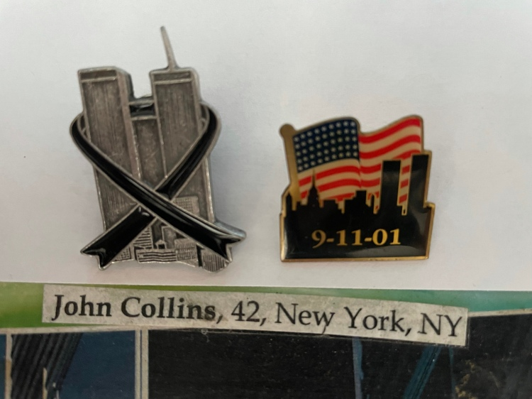 """Two commemorative 9/11 pins. The first a pewter World trade Center with a black ribbon. The second the skyline of New York with the Twin Towers set again an American flag background with the date 9-11-01. A slip of paper reading """"John Collins, 42, New York, NY."""""""